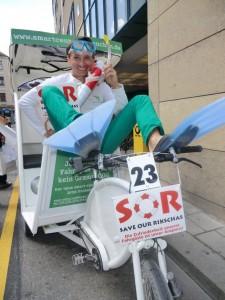 Dominic Staat mit Rettungsring auf einem Rikscha-Mobil